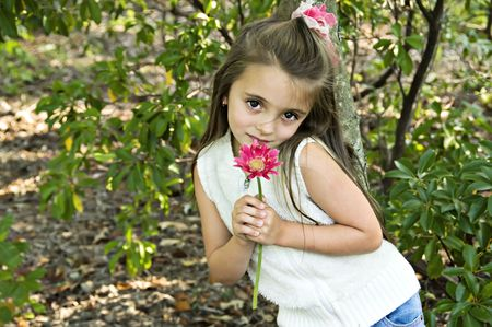 Little girl holding a pink flower in an outdoor setting.
