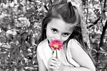 Little girl dressed in white smelling a pretty pink flower. Stock Photo