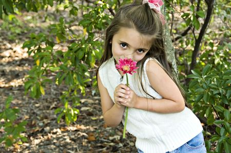 Little girl dressed in white smelling a pretty pink flower