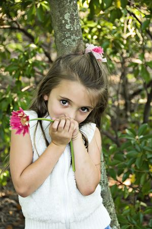 Pretty little shy girl holding a pink flower. Stock Photo