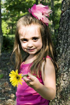 Little girl holding a yellow gerber daisy in an outdoor setting.