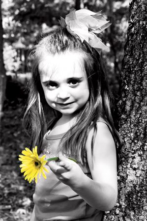 Little girl holding a yellow gerber daisy in an outdoor setting.