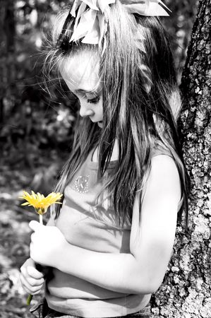 Little girl admiring her yellow flower while leaning against a tree.