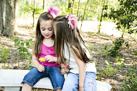 confiding: Two girls sharing secrets in an outdoor setting Stock Photo