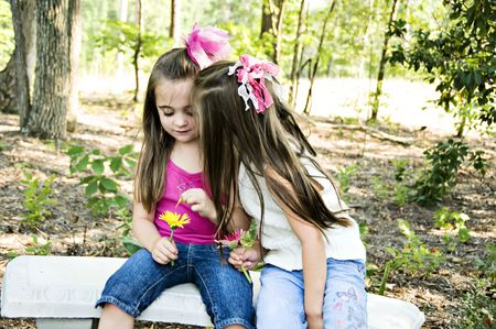 confiding: Two little girls sharing secrets in an outdoor setting.