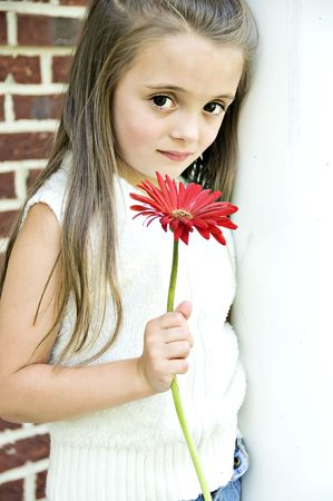 Beautiful Child holding a red flower in her hand. Stock Photo