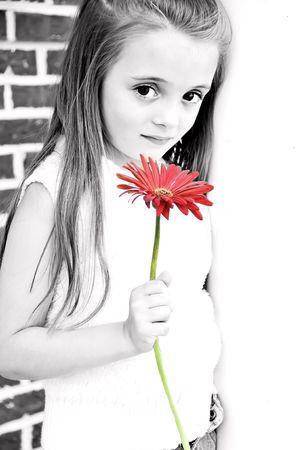 Beautiful Child bedrijf een rode bloem in haar hand.