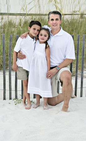 Dad, daughter and son posing for photo on the beach.
