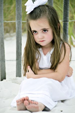 Little girl frowning sitting on the beach by a wooden fence dressed in a white dress with a big bow in her brunette hair.