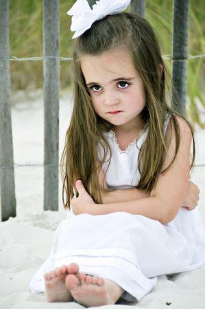 Meisje frowning vergadering op het strand door een houten hek, gekleed in een witte jurk met een grote boog in haar brunette haar. Stockfoto
