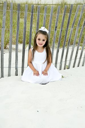 Beautiful young brunettte girl sitting on the sand dressed in a white dress by a wooden fence.