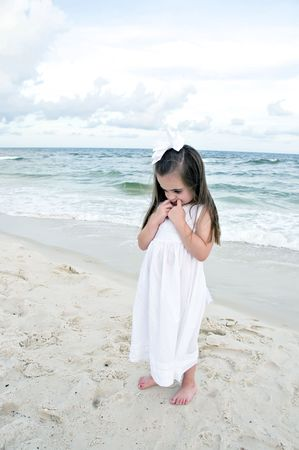 Little girl dressed in white pouting while standing on the beach with the ocean in the . photo