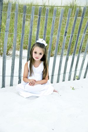 brown  eyed: Pretty little brunette, brown eyed girl, dressed in a white dress, sitting on the beach in the sand.