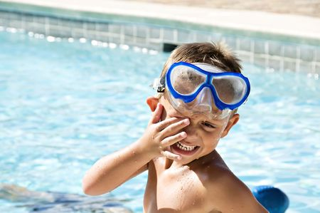 Young boy rubbing his eyes wearing goggles after a swim in the pool.
