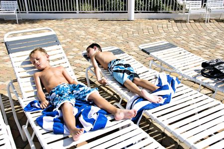 Two little boys sunbathing lying in lounge chairs by a pool.