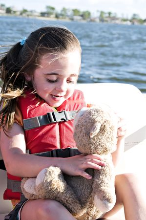 lifevest: Little girl wearing an orange lifevest holding her teddy bear.