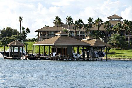 Mooie tropische huis omringd door water, tropische planten, boot en twee huizen.
