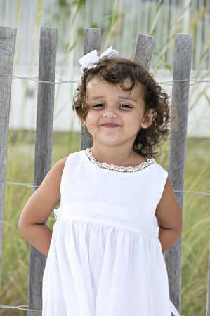 Beautiful little girl standing by a wooden fence on the beach with a silly look on her face.