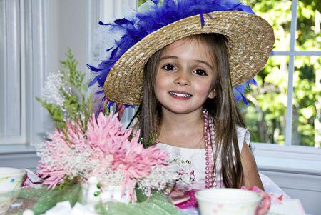 Mooi klein meisje draagt een hoed en kralen partij met een mooie glimlach.