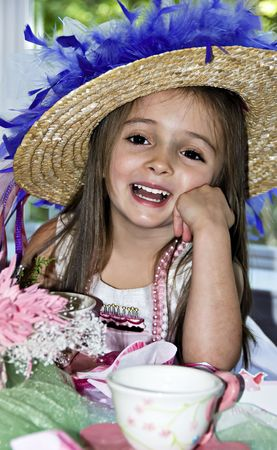 Meisje gekleed voor een thee partij met een mooie hoed en roze kralen.