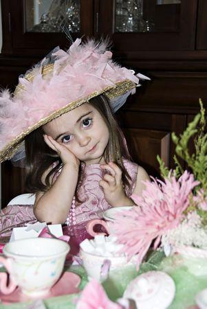 Klein meisje met een geweldige uitdrukking op haar gezicht dragen van een thee partij hoed en roze parels.