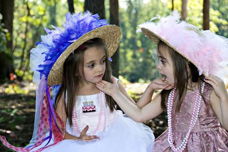 Two little girls dressed for a birthday tea party looking at each other.