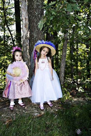 Two little girls dressed up with hats, beads, party dresses and pink sparkle shoes.