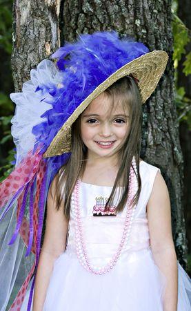 かわいい女の子は彼女の誕生日ドレスアップ パーティーの肖像画のためかなり笑顔します。 写真素材