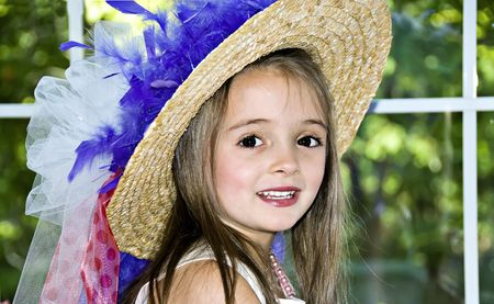 Little girl dressed up in a hat that has ribbons and feathers wrapped around it. Stock Photo