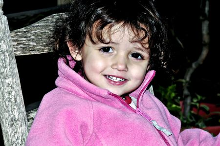 Little girl with perfect  teeth wearing pink.