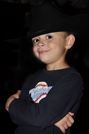 Little boy wearing a cowboy hat and a baseball shirt Stock Photo