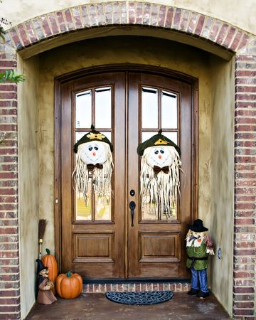 Double Doors decorated with scarecrow faces and other fall decorations. Stock Photo