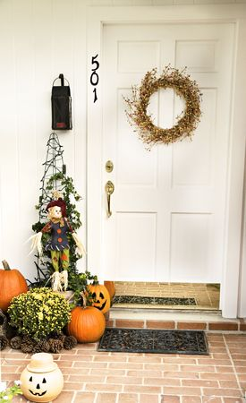 A Fall door adorned with a wreath and surrounded by pumpkins, pinecones and jack-o-laterns. Stock Photo