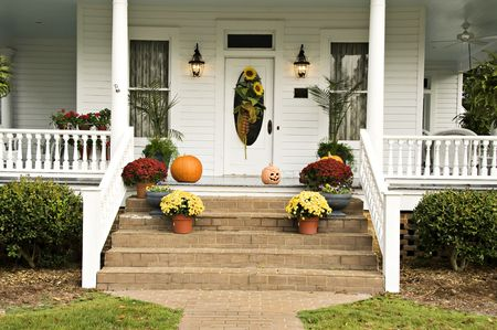 A beautiful front porch decorated for fall with sunflowers, mums, pumpkins, pansies, and a jack-o-latern Stock Photo