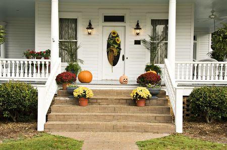 Een mooie veranda ingericht voor vallen met zonnebloemen, moeders, pompoenen, doetjes en een jack-o-latern
