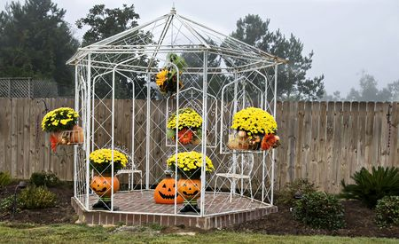 A white iron gazebo decorated for fall with mums, pumpkins and jack-o-laterns overcast by a hazy sky.