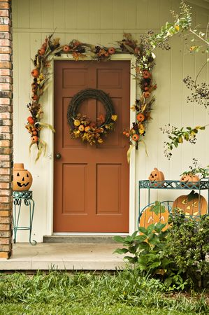 A door decorated with a garland and wreath for fall