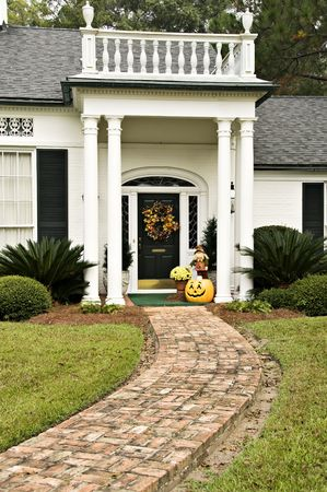 Beautiful entryway decorated for fall with a wreath, mums, scarecrow and pumpkins
