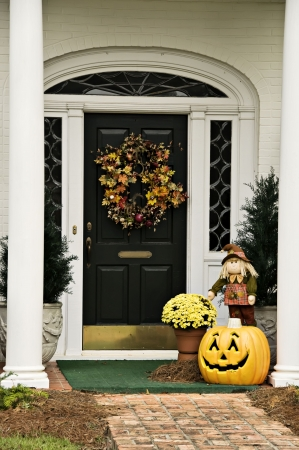 A door decorated with a fall wreath surrounded by fall decorations