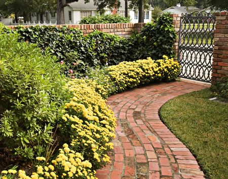 A curved brick path graced with beautiful yellow mums and a garden gate held up with a brick wall.