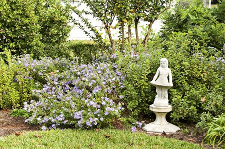 A little girl statues stands proud looking over the blue asters growing in the garden. Stock Photo