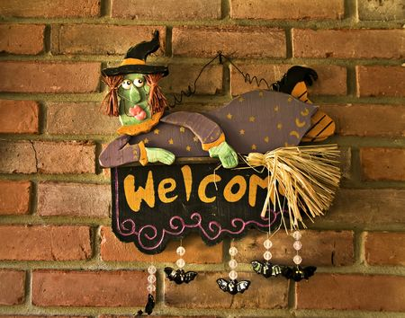 A witch hanging on a brick wall with words of welcome painted on her. photo
