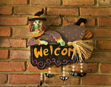 Een heks opknoping op een bakstenen muur met woorden van welkom geschilderd op haar.
