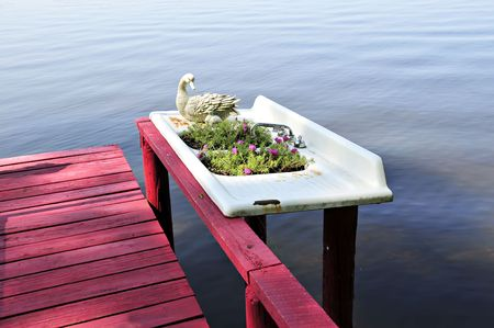 sink drain: Old kitchen or bathroom sink turned into a planter by a lake Stock Photo