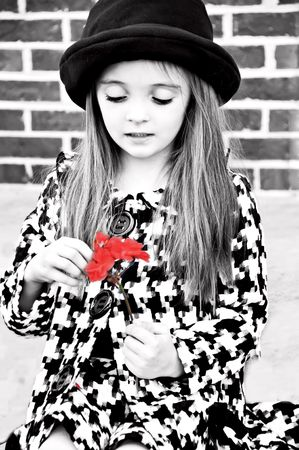 Little girl wearing a hat and holding a flower