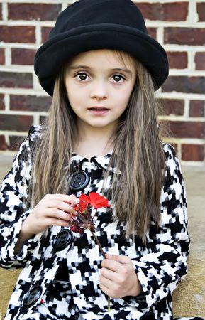 Klein meisje draagt een jas en hoed bedrijf een bloem