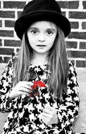 Het dragen van een jas en hoed bedrijf een bloem klein meisje