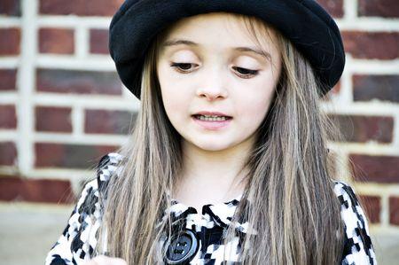 Little girl wearing a hat looking shy