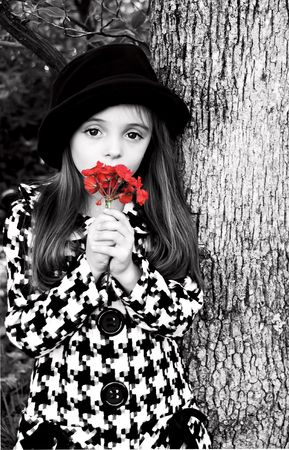Little girl standing by a tree wearing a coat and hat holding a flower.