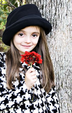 Little girl dressed in a hat and coat holding a red flower photo